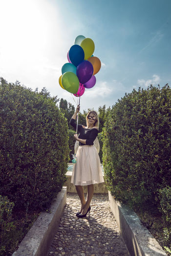 Woman With Colorful Balloons On Walkway Against Sky