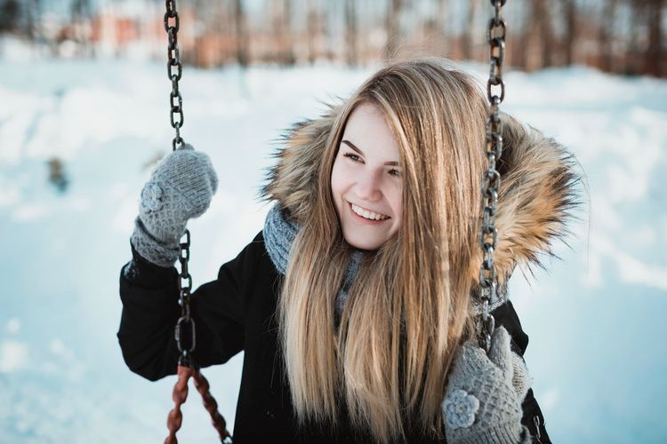 Smiling young woman swinging during winter