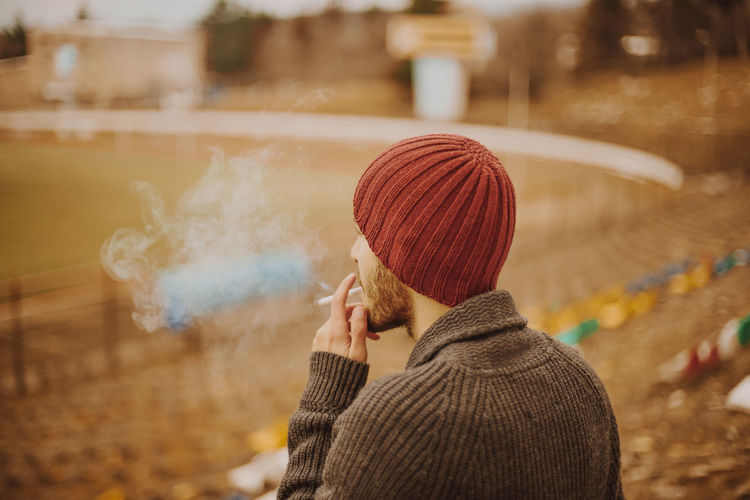 Man wearing warm clothing while smoking cigarette outdoors