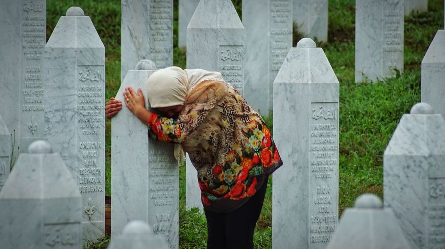Mother by her child's grave in Srebrenica Sadness Srebrenica Bosnia And Herzegovina War Solitude And Silence Real People Women People Day Clothing Standing Traditional Clothing Adult Rear View Grave Cemetery Tombstone Outdoors The Photojournalist - 2019 EyeEm Awards