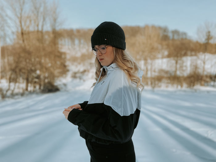 Side view of woman standing in snow