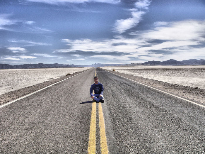 Man sitting on road leading towards mountains against blue sky