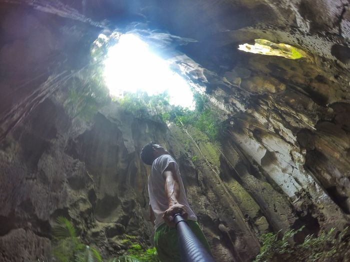 Low Angle View Of Man Standing Against Rock Formation In Cave