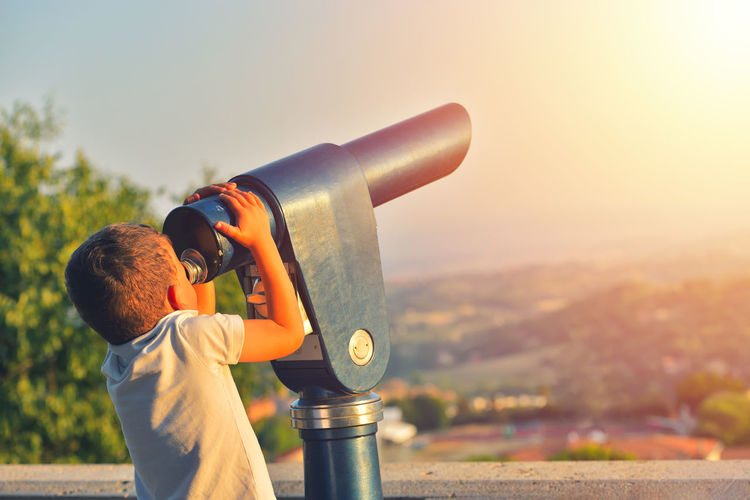 Boy looking through coin-operated binoculars against sky during sunset