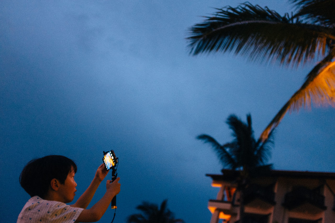 Side View Of Boy Photographing From Mobile Phone On Monopod Against Sky