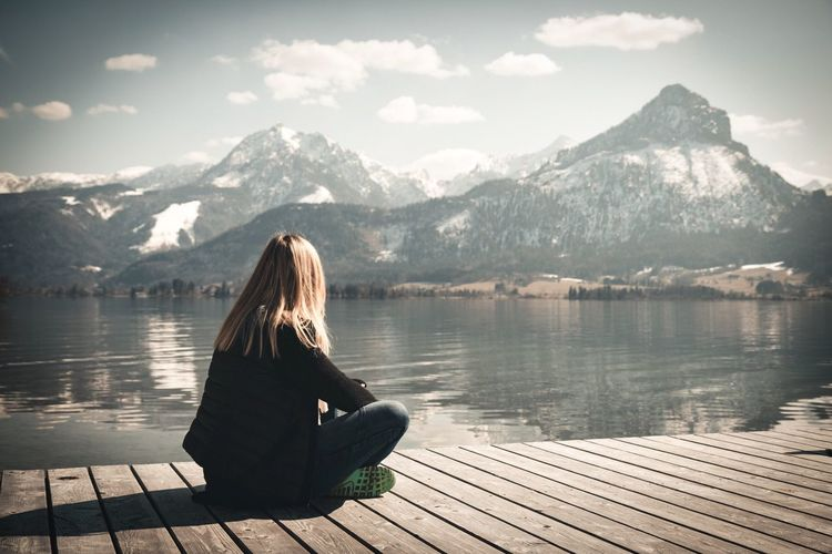 Woman sitting on lake by mountains against sky