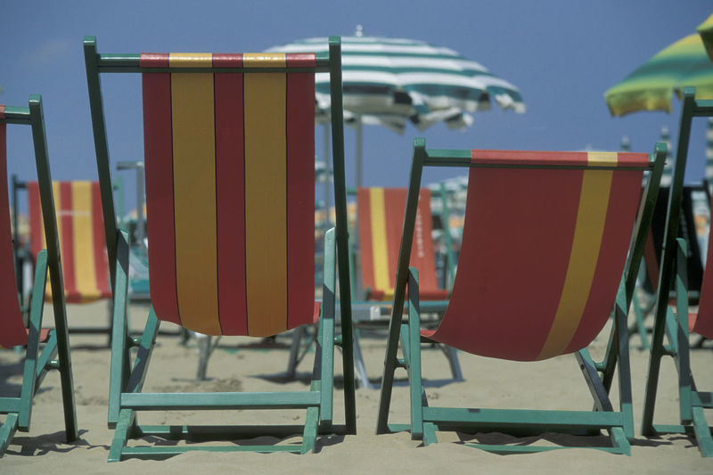 Close-up of empty chairs at beach against sky