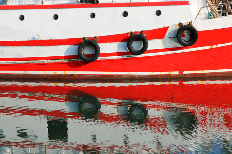 large red and white ship moored in the harbor Fishing Boats Harbor Mirror Red Reflection On Water Transportation Travel Boat Commercial Dock Fishing Fishing Boat Mirror In The Water Mirror On Water Moor  Moored Mooring Ocean Ocena Portrait Reflect On Water Sailing Sea Shipping  Vessel Vessel In Port