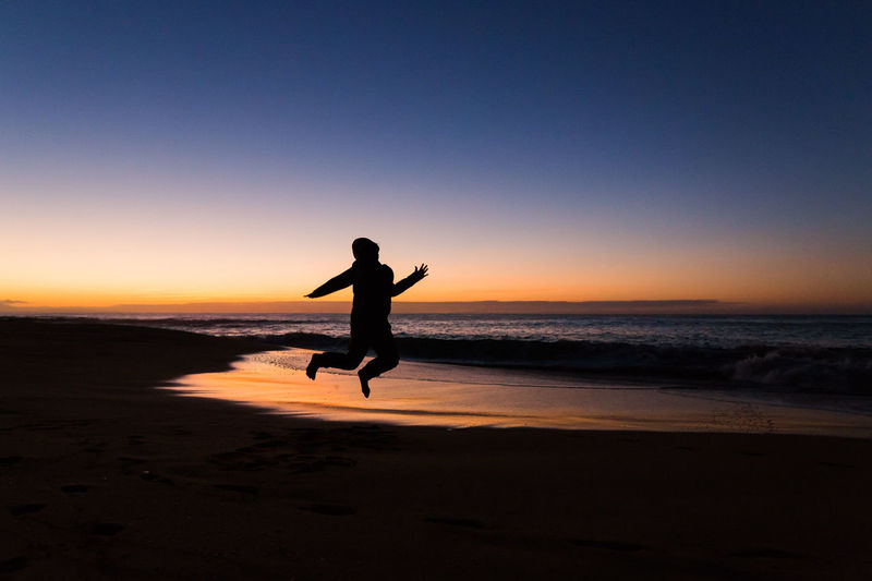 Silhouette boy jumping at beach against sky during sunset