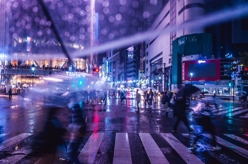 Blurred motion of people walking on wet street in city at night