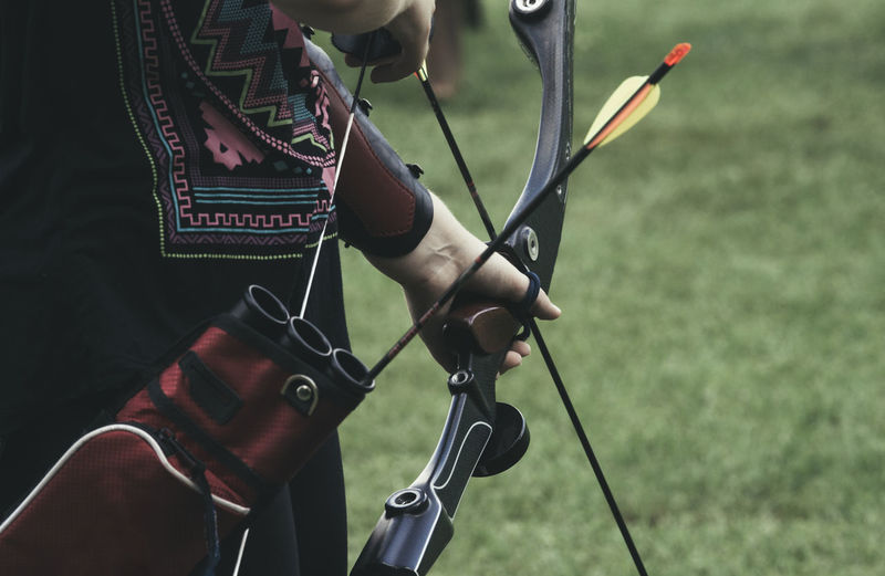 Midsection Of Woman Holding Bow And Arrow On Field