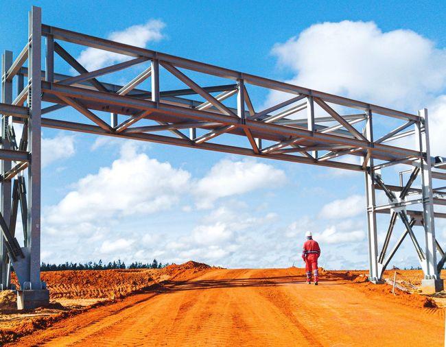 Worker walking down a bridge