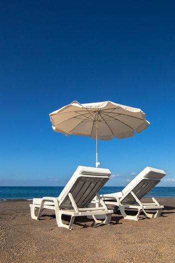 Deck chairs on beach against clear blue sky