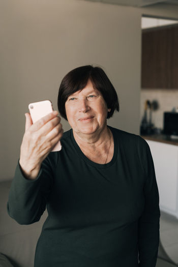 Senior woman using smart phone standing at home
