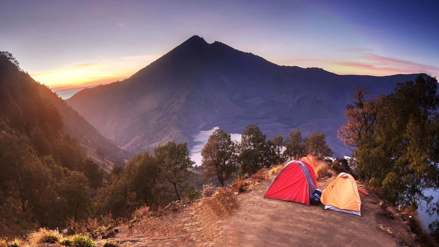 Tents on the rim of the mount Rinjani or Gunung view Crater, Anak Rinjani and lake view of Mount Rinjani from Senaru rim. ASIA Holidays INDONESIA Mount Rinjani Tourist Attraction  Background Photography Beauty In Nature Blue Sky Forest Golden Hour Hikers Landscape Lombok Mountain Mountain Range Outdoors Scenics Segara Anak Lake Sembalun Crater Rim Senaru Crater Rim Sunrise Sunset Tourist Destination