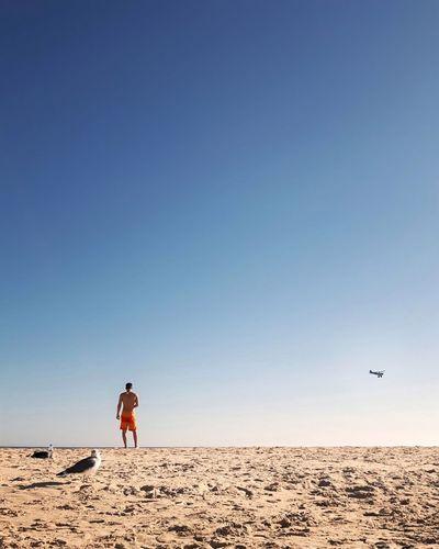Man standing on beach against clear blue sky