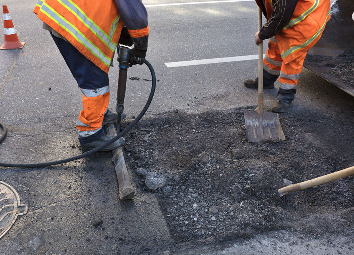 Low section of men working on street in city