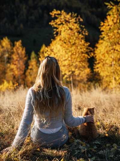 Rear view of woman sitting on tree during autumn