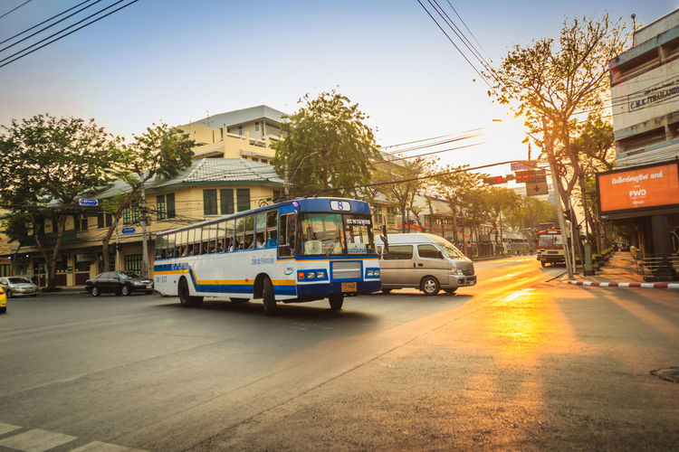 Bangkok, Thailand - March 2, 2017: Local bus and cars in traffic passes through a busy junction during sunset in Bangkok, Thailand. Junction Sunset And Clouds  Traffic Traffic Jam Traffic Signs Architecture Building Building Exterior Built Structure Car City City Street Junctionsquare Land Vehicle Local Bus Mode Of Transportation Motion Motor Vehicle Nature No People Outdoors Plant Residential District Road Sky Street Sunlight Sunset Traffic Arrow Sign Traffic Light  Traffic Lights Traffic Sign Traffic Signal Trafficjam Transportation Tree