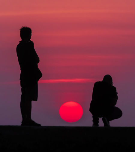 Silhouette couple standing against orange sky during sunset