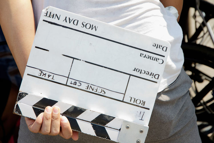 Close-up of man holding clapper board