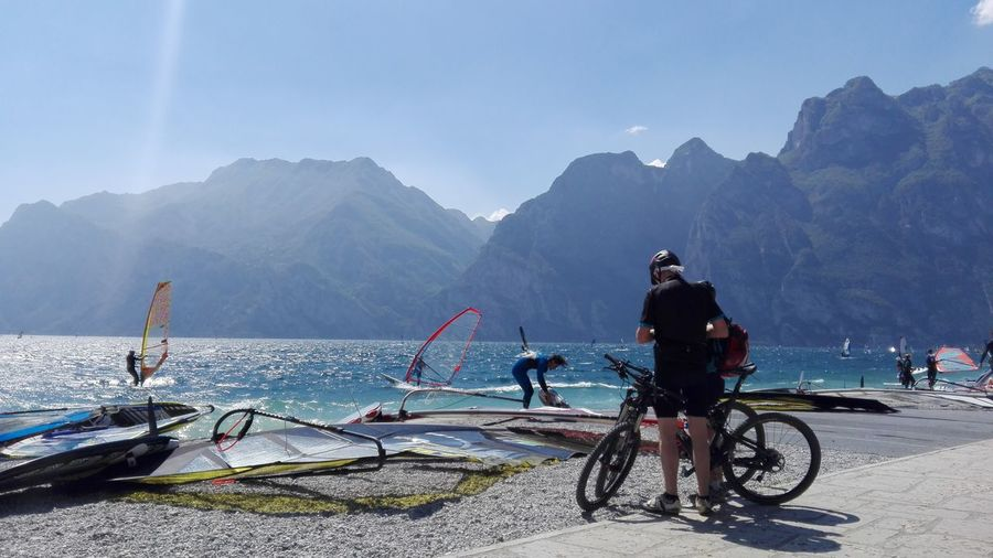 Cyclists and windsurfers in torbole lake, italy