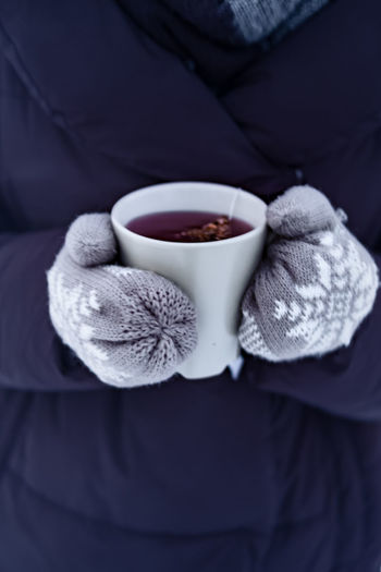 The girl holding a cup of hot tea in winter time, holidays season Christmas Time Hot Tea Hot Beverage Close-up Coffee - Drink Coffee Cup Cozy Moments Cup Drink Drinking Food And Drink Freshness Holding Human Body Part Human Hand Indoors  Midsection One Person One Woman Only Refreshment Tea - Hot Drink Warm Clothing Winter Drinks Winter Season Wool
