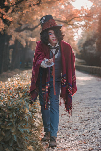 Full length of man cosplaying mad hatter standing in park during autumn
