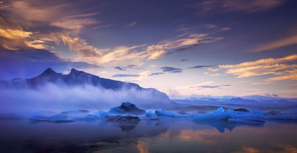 Huge ice glaciers in a water colored by the beautiful sunset