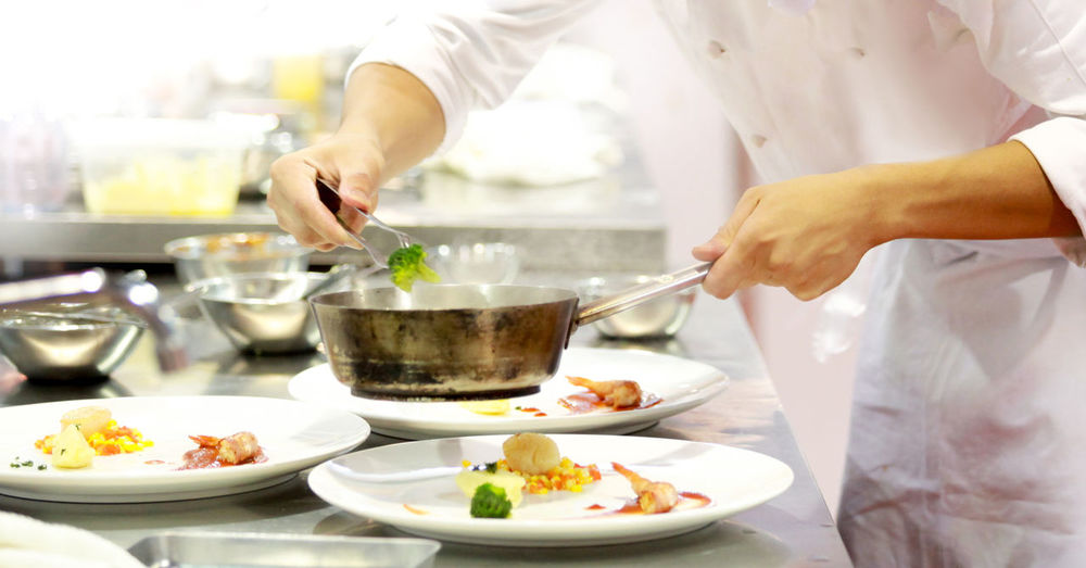 Cropped image of chef styling food in plate