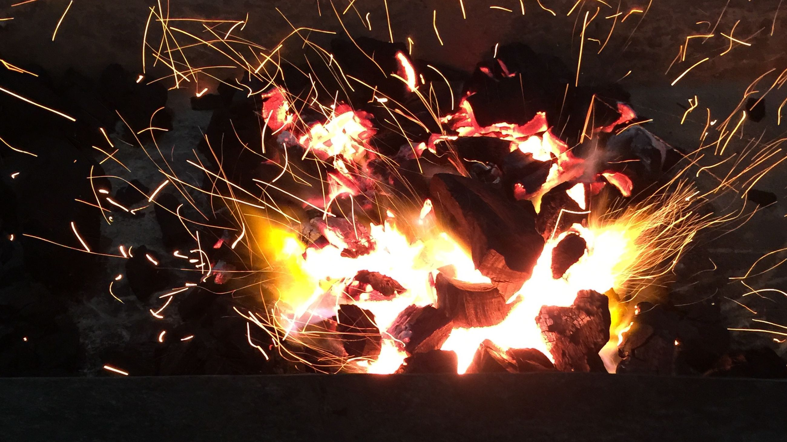 night, illuminated, glowing, fire - natural phenomenon, burning, celebration, motion, flame, long exposure, heat - temperature, firework display, bonfire, dark, sparks, firework - man made object, exploding, orange color, outdoors, light - natural phenomenon, arts culture and entertainment
