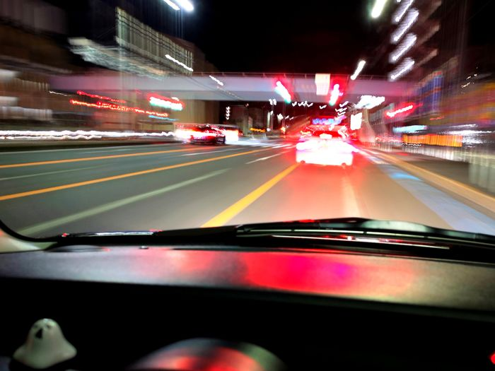 Cars on road in city seen through car windshield