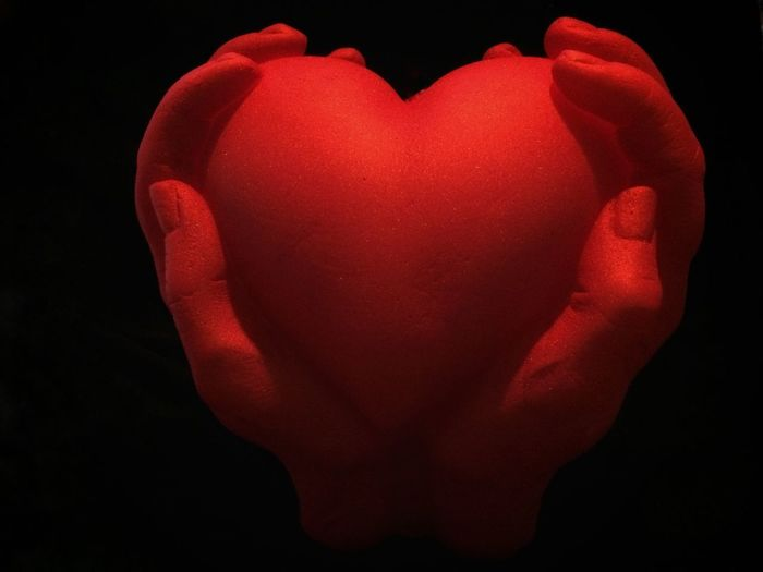 Close-up of hand holding heart shape against black background