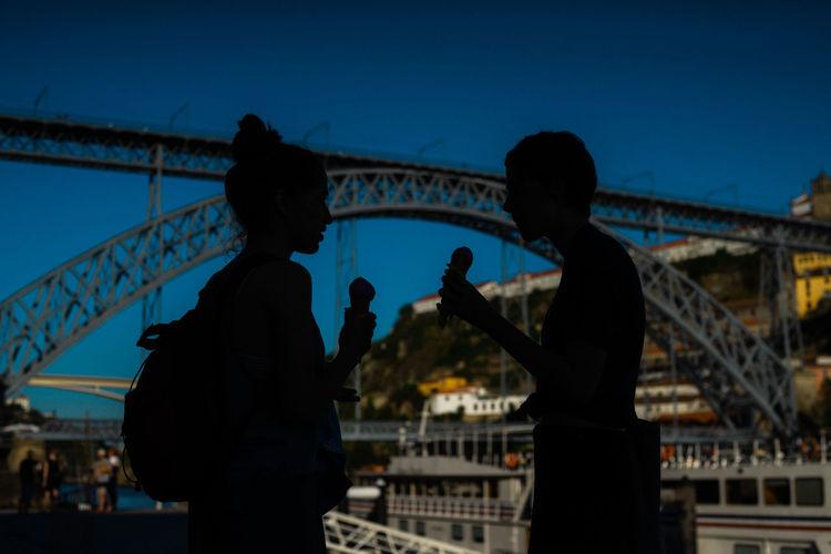 Silhouette people on bridge against sky in city at dusk