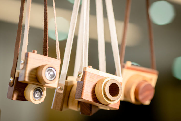 Close-up of wooden cameras hanging for sale in store