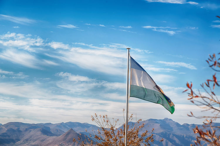 Low angle view of flag on mountain against sky