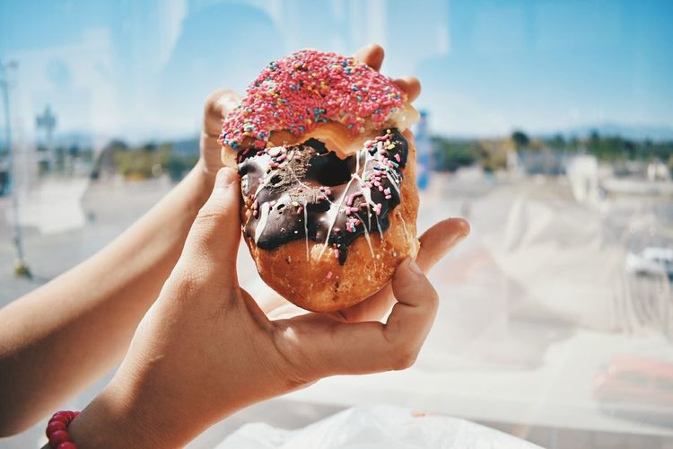 Close-up of hand holding a donut