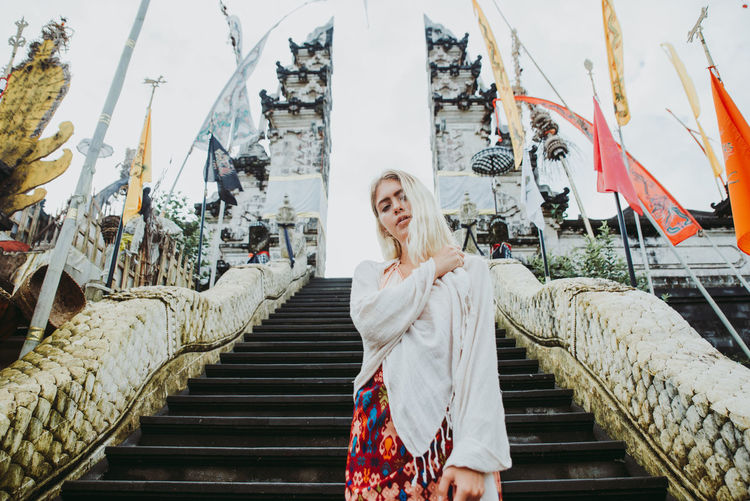 Young woman standing on staircase at temple gate