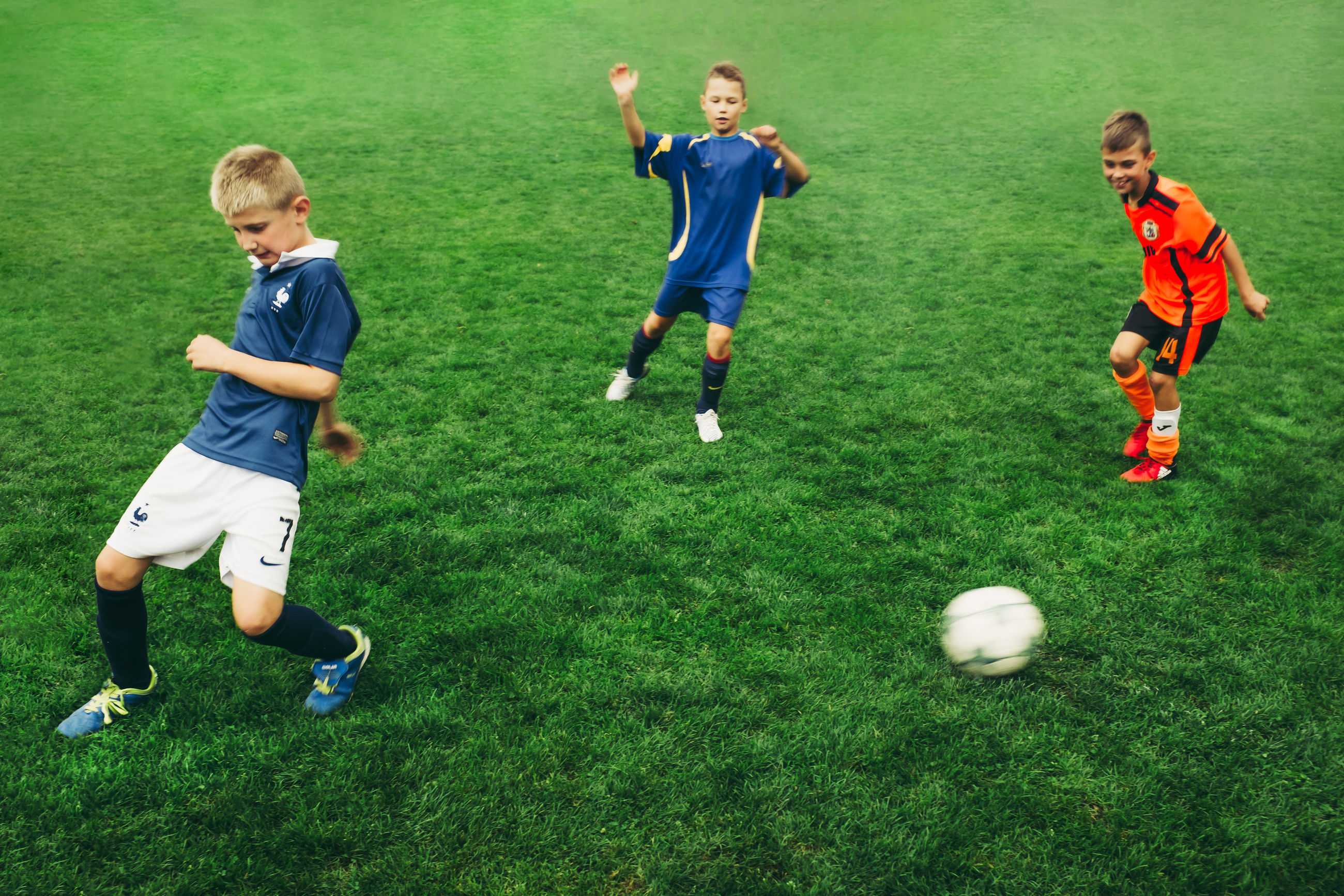 childhood, children only, soccer, boys, full length, child, grass, sport, playing, three people, soccer uniform, togetherness, sports team, day, soccer player, soccer ball, fun, motion, friendship, only boys, sports clothing, outdoors, sports uniform, soccer field, teamwork, people