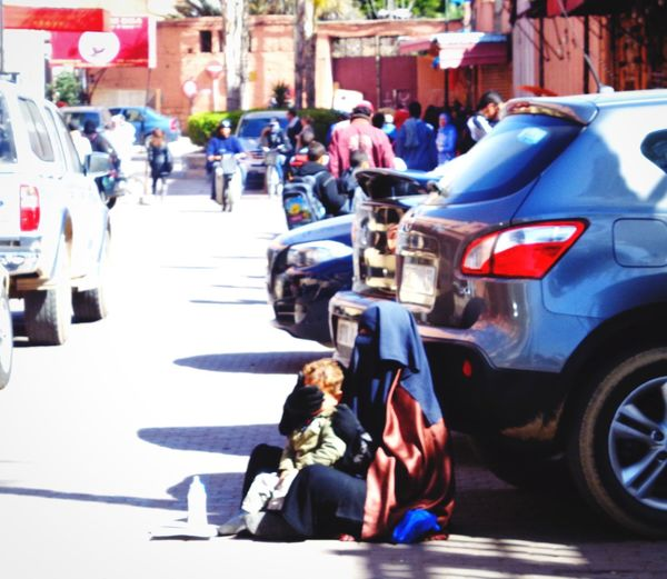 Protective instincts Beggar Beggar Woman Care Instict Protection Mother And Son City Street Car Motor Vehicle Real People Mode Of Transportation Transportation Women Child City Life Outdoors Day