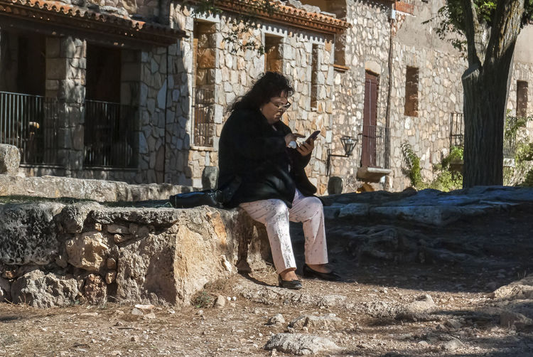 Woman using mobile phone while sitting against building