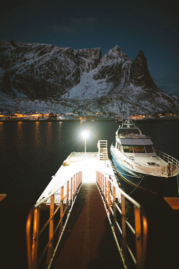 waiting for my ride. find more travel inspiration at https://www.instagram.com/simonmigaj Norge Norway Reine Travel Adventure Fjord Illuminated Mountain Mountain Range Nature Nautical Vessel Night Outdoors Scenics Snow Tranquility Transportation Water Winter