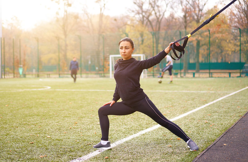 Portrait of smiling woman exercising at park