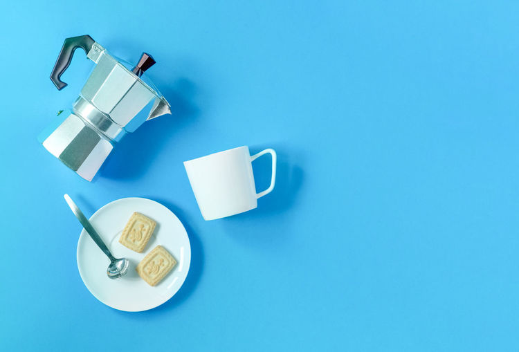 High angle view of coffee cup against blue background