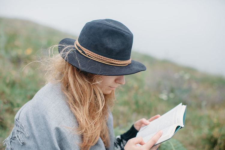 Young woman in hat reading book on field against sky