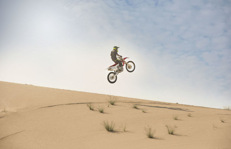 Low angle view of man riding motorcycle at desert