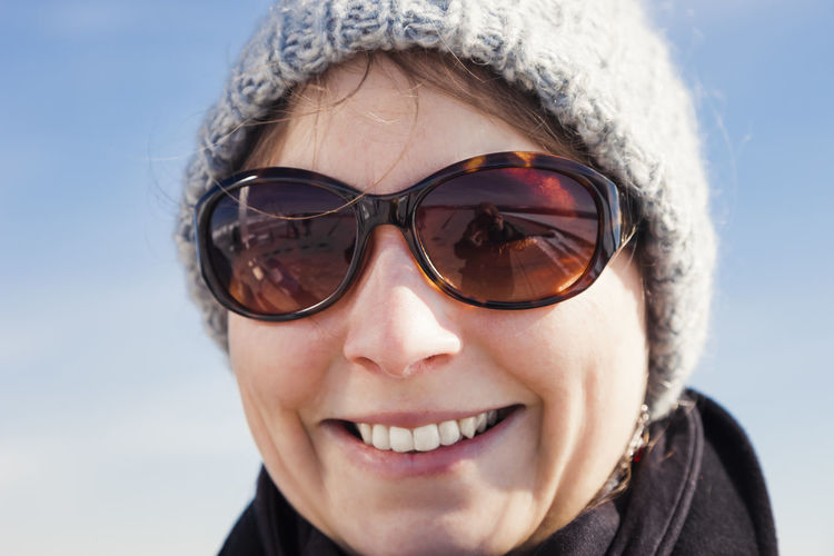 Close-up portrait of smiling woman wearing sunglasses against sky