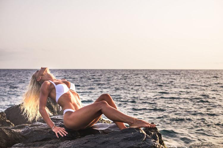 Sensuous woman wearing bikini while sitting on rocks against sea during sunset