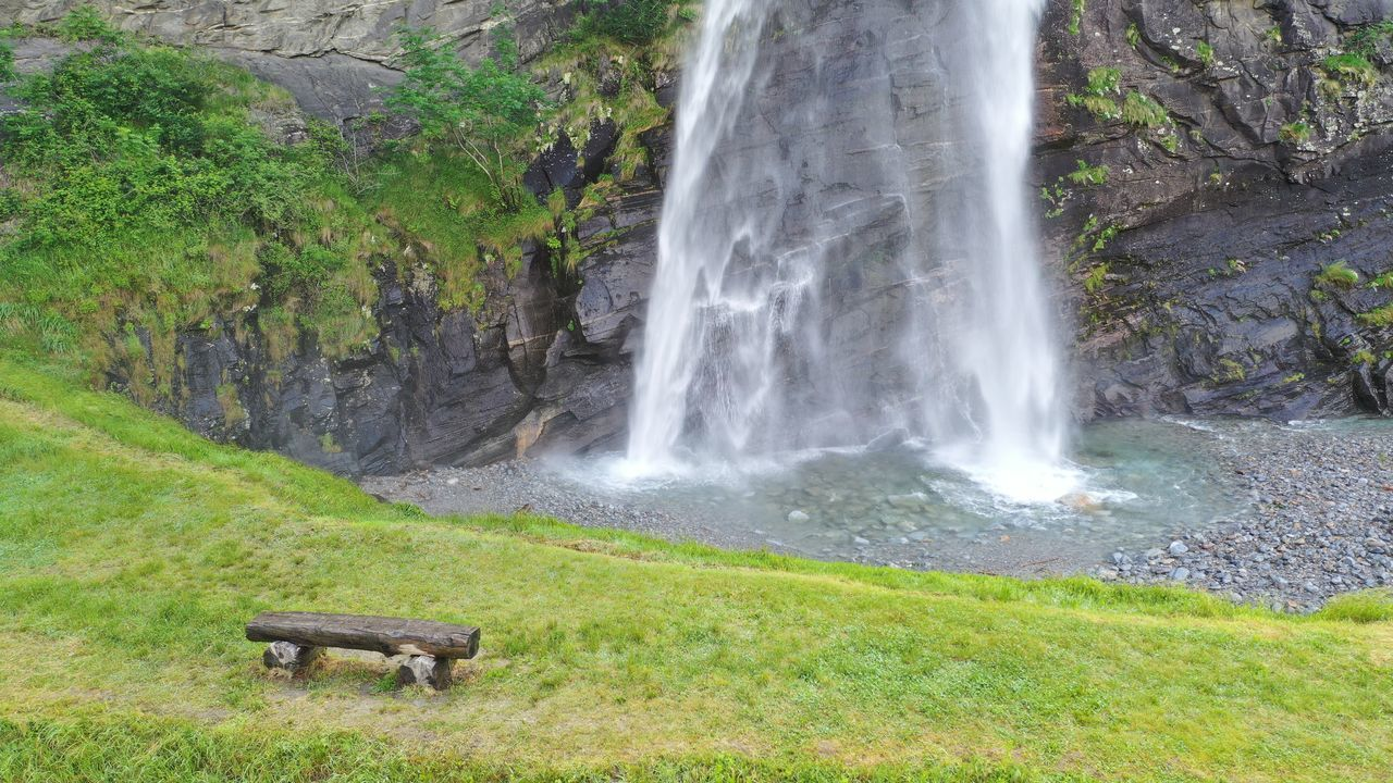 SCENIC VIEW OF WATERFALL ON SUNNY DAY