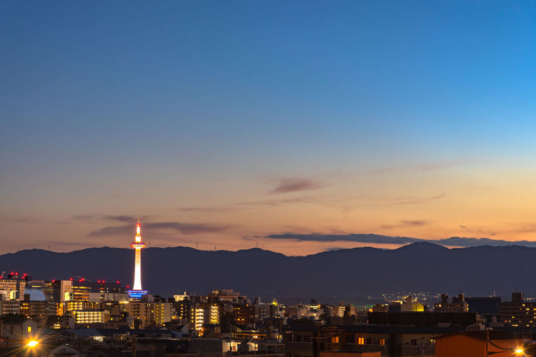 Colorful Kyoto Tower with Kyoto city skyline view at dusk in Japan Kyoto Tower Japan Landmark Famous Place Japanese  Kyoto Japan Kyoto Tower Building Architecture City Sky Skyline Cityscape Tourism Tourist Backgrounds Capital Letter Illuminated Night Evening Dusk Sunset Kansai Destination District Downtown ASIA Asian  Beautiful Scenery Scenics Station Travel Twilight Urban View Attraction Sightseeing Skyscraper Street Symbol Commercial Observation Point Landscape Light Up High Angle View Buildings Outdoors Nature